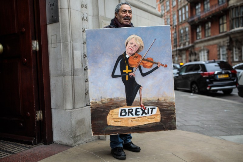 The political artist Kaya Mar stands with his painting depicting Prime Minister Theresa May playing a violin in Westminster on Jan 16. (Jack Taylor/Getty Images)