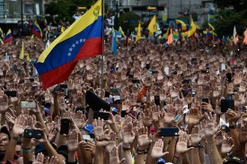 People raise their hands during a mass opposition rally against President Nicolás Maduro in Caracas on Jan. 23. (Federico Parra/AFP/Getty Images)
