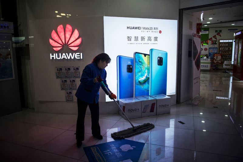 A cleaner in front of a store selling Huawei products in Beijing on Jan. 29. (Kevin Frayer/Getty Images)