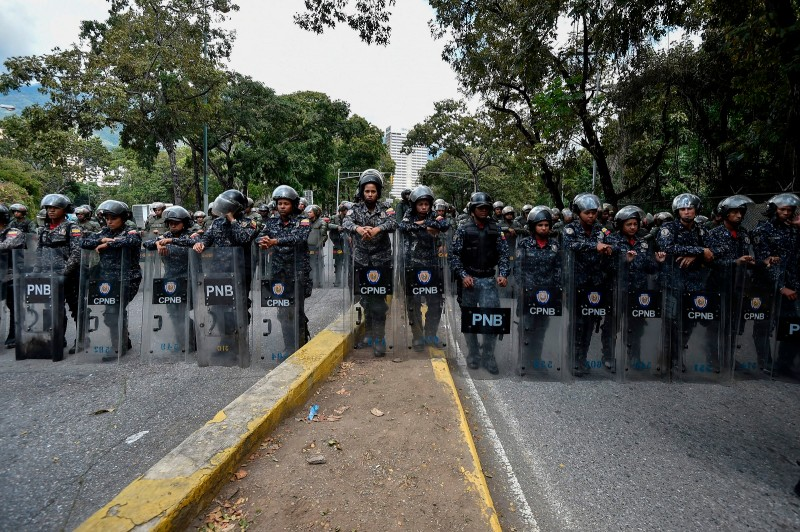Members of the Bolivarian National Police (PNB) line up to guard the entrance of Venezuela's Central University (UCV) in Caracas, during a protest against the government of President Nicolas Maduro on January 30, 2019. (LUIS ROBAYO/AFP/Getty Images)