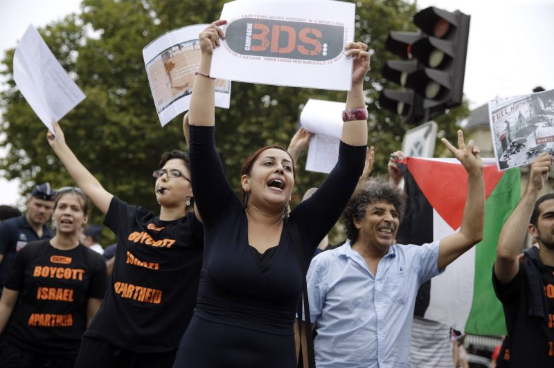 """A pro-Palestinian protester holds a placard reading """"BDS"""" (boycott, divestment, sanctions) at an event celebrating Tel Aviv in central Paris on Aug. 13, 2015. (Kenzo Tribouillard/AFP/Getty Images)"""