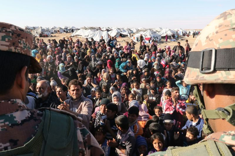 Syrian refugees, stuck between the Jordanian and Syrian borders, wait to cross into Jordan at the Hadalat border crossing on Jan. 14, 2016. (Khalil Mazraawi/AFP/Getty Images)