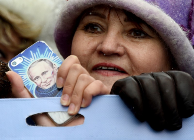 A woman holds a smartphone bearing an image of Russian President Vladimir Putin as pro-Kremlin supporters celebrate National Unity Day in central Moscow on Nov. 4, 2016. (Vasily Maximov/AFP/Getty Images)