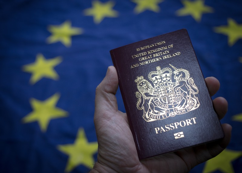 A man holds a British passport in front of the flag of the European Union on Oct. 13, 2017 in Bath, England. (Matt Cardy/Getty Images)