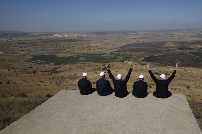 Druze men at the Israeli-annexed Golan Heights flash the V for victory sign as they look out across the southwestern Syrian province of Quneitra on July 7, 2018. (Jalaa Marey/AFP/Getty Images)