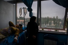 An 11-year-old girl cares for her mother as she receives her first dose of chemotherapy at Jamhuriat Hospital in Kabul on July 15, 2017. When 38-year-old Fatema was diagnosed with breast cancer, it took her seven months to gather the money needed for her surgery, and she was forced to delay follow-up treatment until she could borrow money to pay for it. (Kiana Hayeri for Foreign Policy)