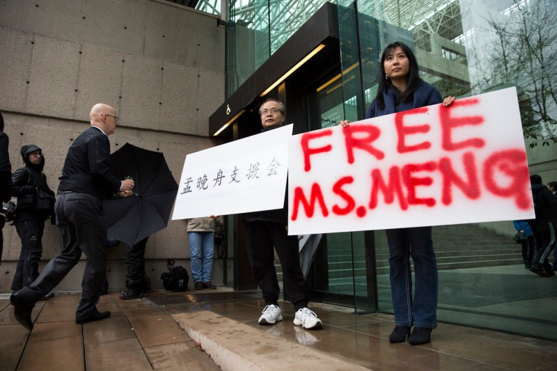 Protesters hold signs in favor of Huawei Technologies Chief Financial Officer Meng Wanzhou outside her bail hearing at British Columbia Superior Courts in Vancouver following her arrest in Canada for extradition to the United States on Dec. 11, 2018.