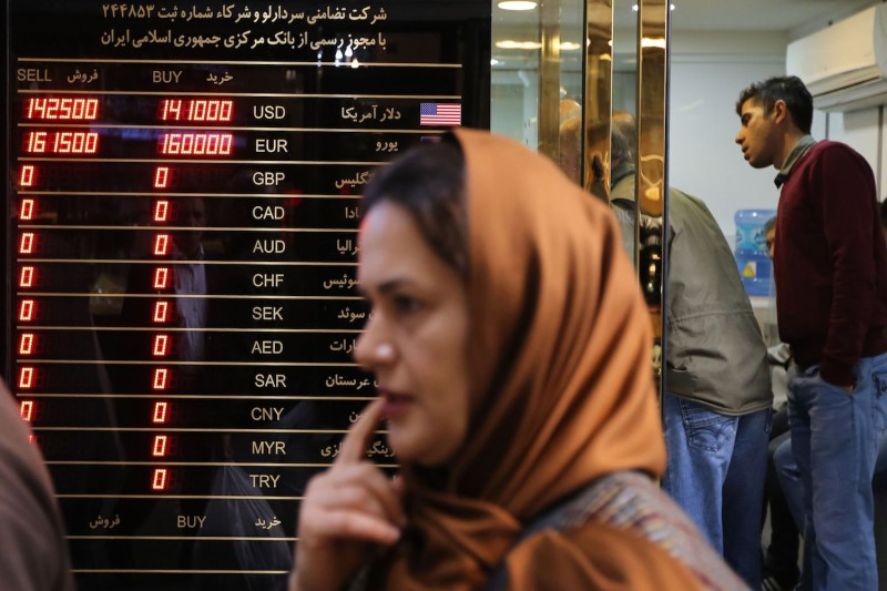 A woman walks past a currency exchange shop in Tehran's grand bazaar on Nov. 3, 2018.