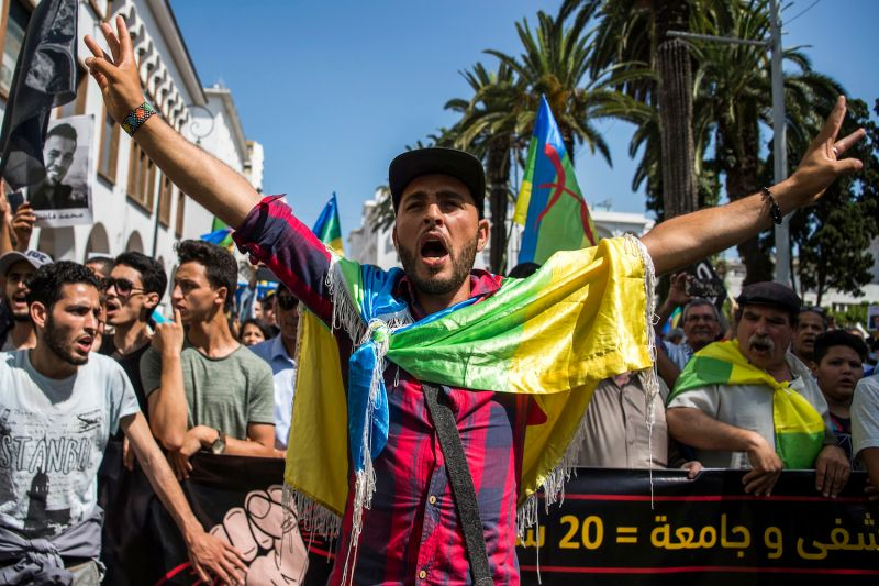 "A Moroccan draped in the Berber, or Amazigh, flag shouts slogans while marching during a protest against the jailing of Al-Hirak or ""Popular Movement"" activists in the capital Rabat on July 15, 2018."