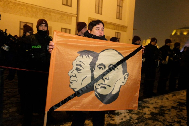 A participant holds a banner with photos of Russian President Vladimir Putin and Hungarian Prime Minister Viktor Orban in front of the presidential palace during a demonstration on Dec. 21, 2018.