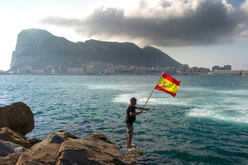 A fisherman holds a Spanish flag during a protest in the bay of Algeciras, near the Rock of Gibraltar, on August 18, 2013.