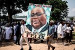 Supporters of Felix Tshisekedi, the newly elected president of the Democratic Republic of the Congo, hold his portrait and cheer during his inauguration in Kinshasa on Jan. 24. (John Wessels/AFP/Getty Images)