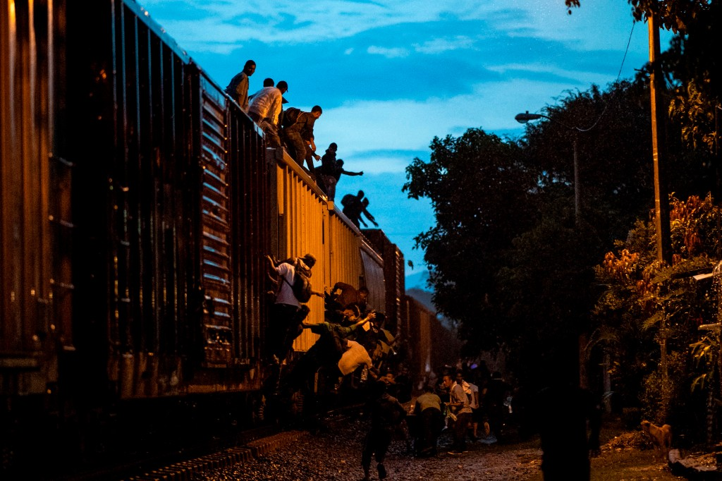 Undocumented migrants climb on a train known as La Bestia in Las Patronas, Veracruz state, Mexico, to travel through Mexico to reach the United States on Aug. 9, 2018. (Ronaldo Schemidt/AFP/Getty Images)