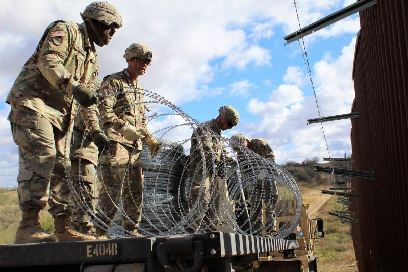 Engineers from the 937th Clearance Company prepare to place concertina wire on the Arizona-Mexico border wall on Dec. 1, 2018. (U.S. Army photo by 2nd Lt. Corey Maisch)