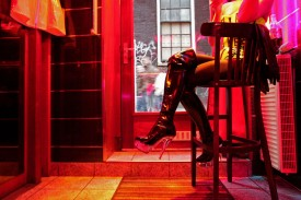 A prostitute waits for clients behind her window in the red light district of Amsterdam on Dec. 8, 2008.