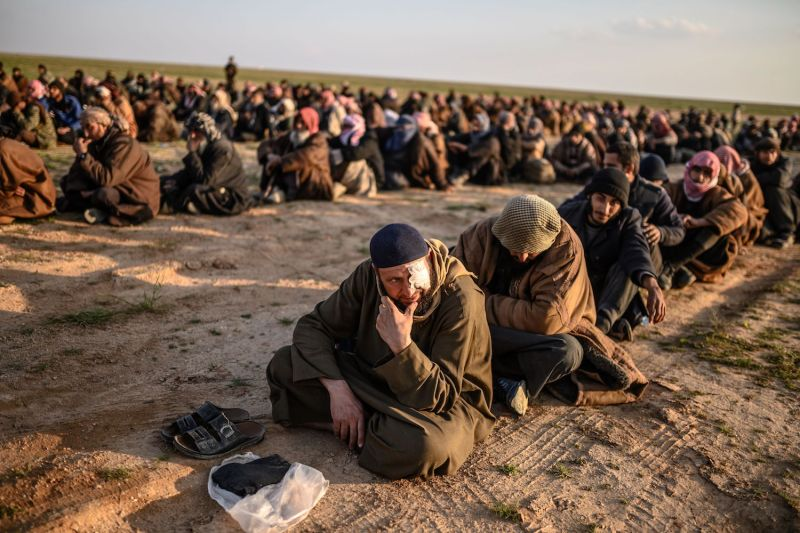 Men suspected of being Islamic State fighters wait to be searched by members of the Kurdish-led Syrian Democratic Forces after leaving the group's last holdout of Baghouz, Syria, on Feb. 22. (Bulent Kilic/AFP/Getty Images)