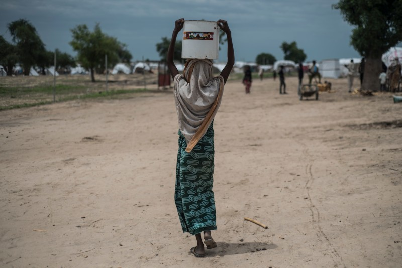 A woman carries a pot of water on her head in Rann in north-east of Nigeria close to the Cameroonian border on July 29, 2017.