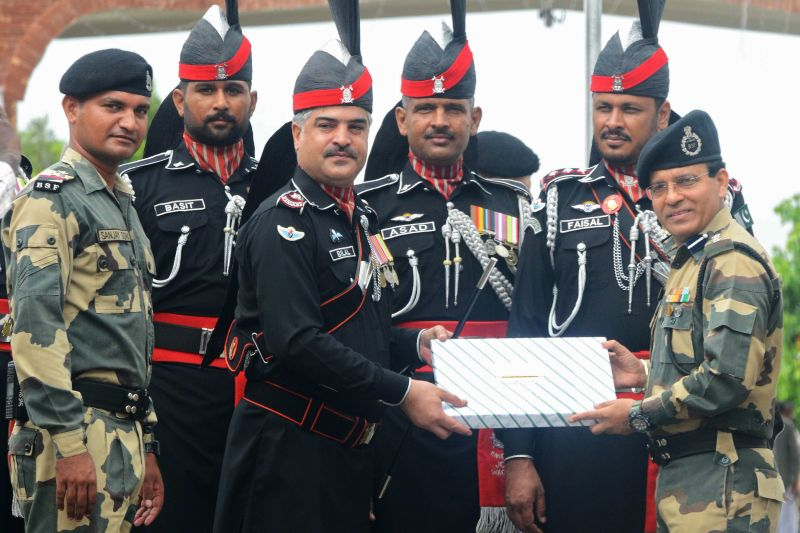 Pakistani Wing Commander Bilal presents sweets to Indian Border Security Force Commandant Sudeep during a ceremony to celebrate Pakistan's Independence Day at the India-Pakistan Wagah border post on Aug. 14, 2018. (Narinder Nanu/AFP/Getty Images)