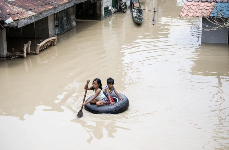 Children use a tire to cross a flooded street in the aftermath of Super Typhoon Mangkhut in the Philippines on Sept. 16, 2018. (Noel Celis/AFP/Getty Images)