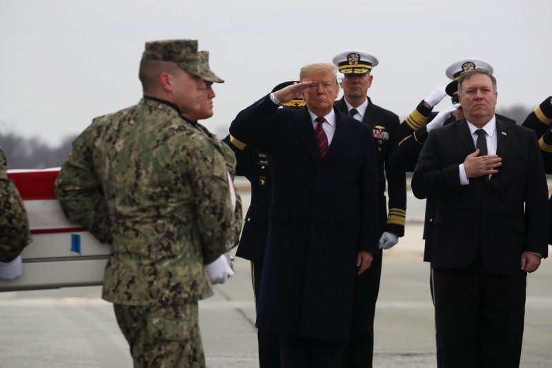 President Donald Trump salutes while joined by Secretary of State Mike Pompeo as a military carry team moves the transfer case containing the remains of Scott A. Wirtz during a dignified transfer at Dover Air Force Base, Jan. 19, 2019 in Dover, Delaware. (Mark Wilson/Getty Images)