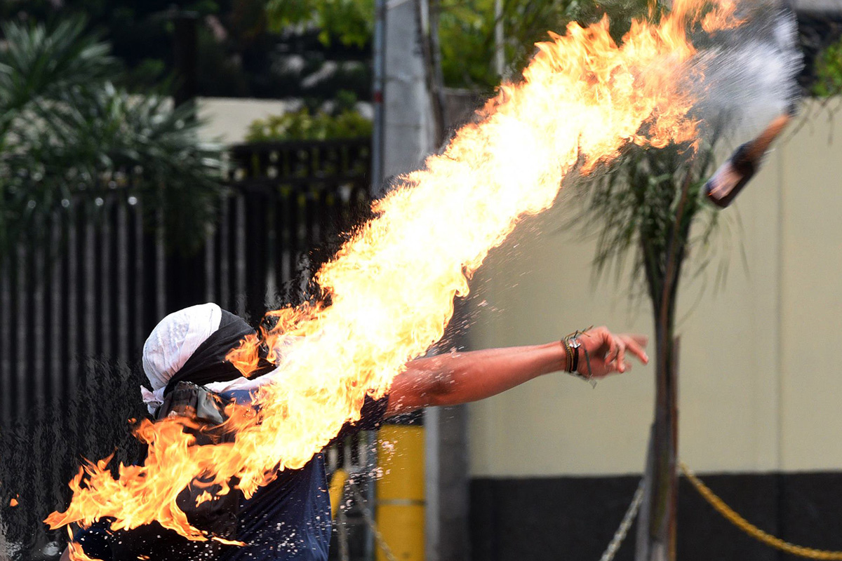 A university student throws a Molotov cocktail at riot police during a protest demanding the resignation of Honduran President Juan Orlando Hernandez in Tegucigalpa on Jan. 28. Hernandez took office on Jan. 27 after being re-elected in a vote called fraudulent by the opposition alliance. (Orlando Sierra/AFP/Getty Images)