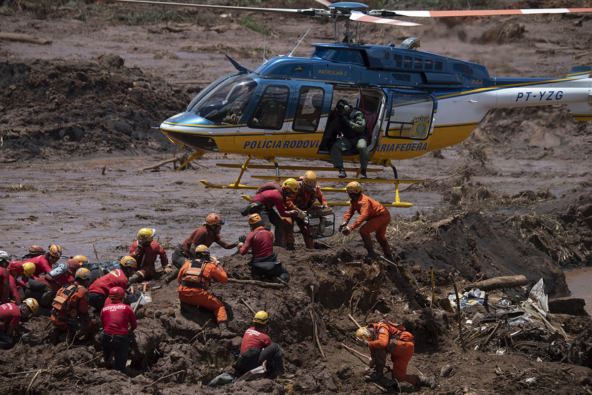 Firefighters receive equipment to open a vehicle found in the mud as they search for victims of a dam collapse at an iron-ore mine belonging to Brazil's giant mining company Vale near the town of Brumadinho in southeastern Brazil on Jan. 28. More than 100 people were confirmed dead as hopes faded about more than 200 still missing. (Mauro Pimentel/AFP/Getty Images)