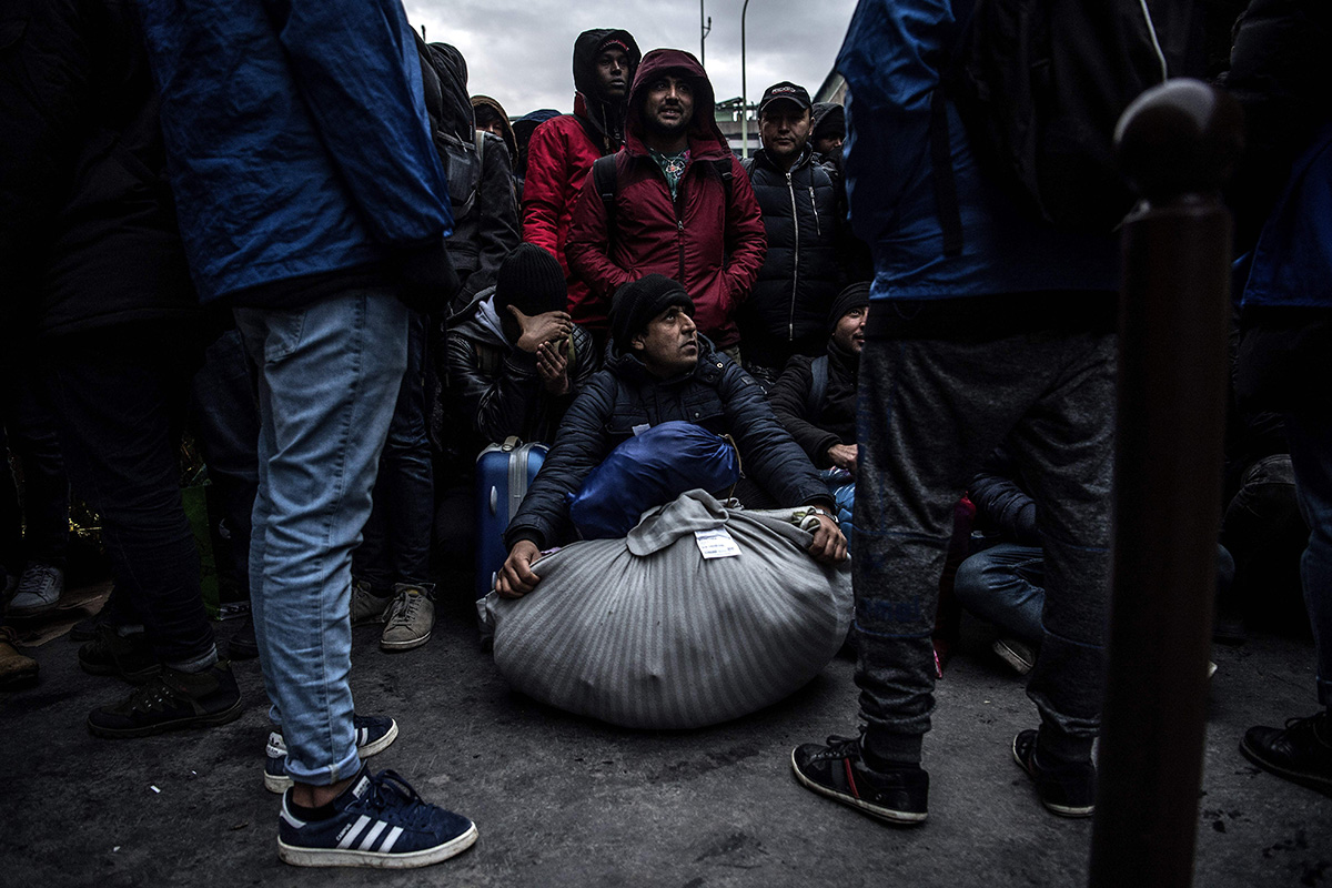 Migrants wait at a makeshift camp under Paris' ring road in the north of Porte de la Chapelle on Jan. 29. (Christophe Archambault/AFP/Getty Images)
