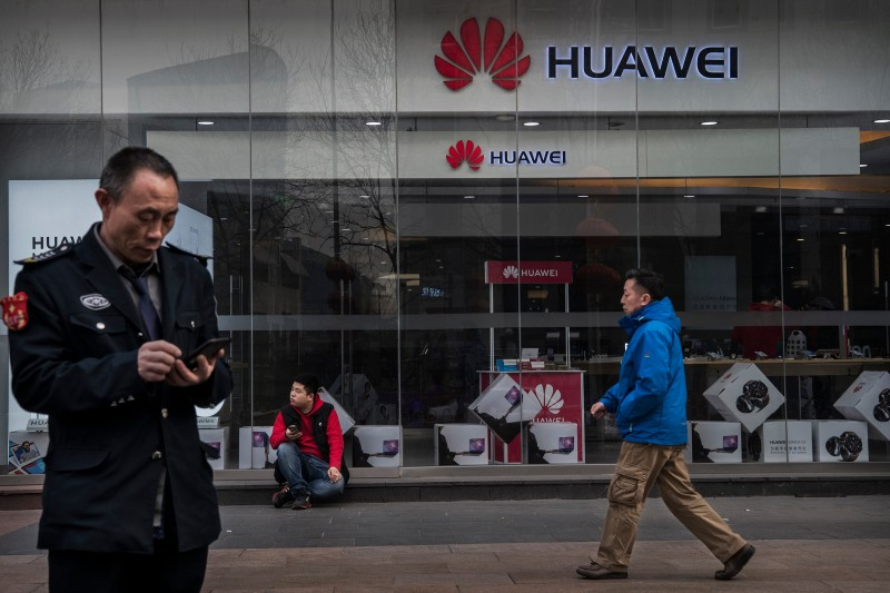 Chinese pedestrians walk past a Huawei store in Beijing on Jan. 29. (Kevin Frayer/Getty Images)