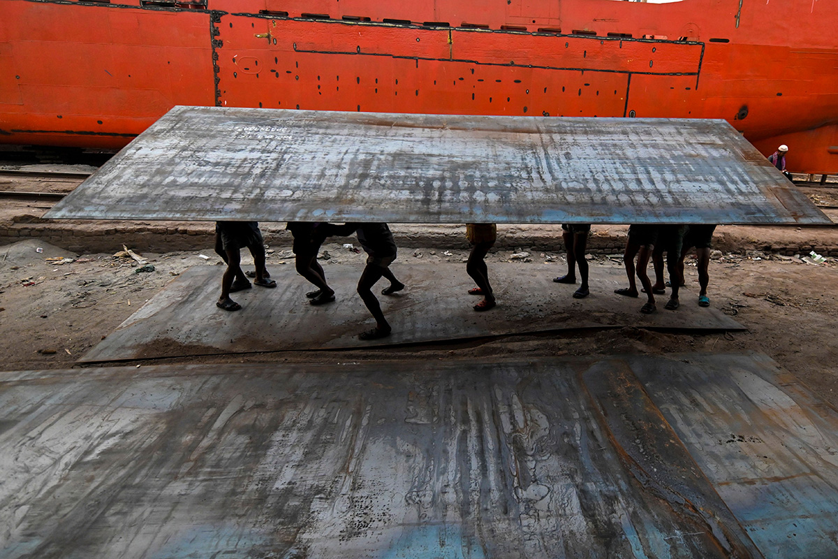 Bangladeshi laborers carry a heavy steel plate in a dockyard in Dhaka on Jan. 29. (Munir Uz Zaman/AFP/Getty Images)