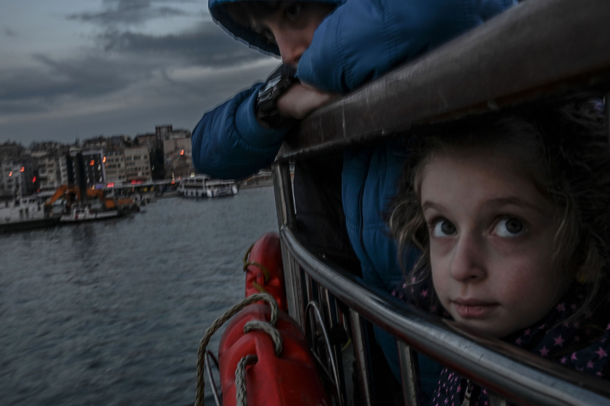 A little girl looks past her brother at the back of Kadikoy ferry in Istanbul on Jan. 29. (Bulent Kilic/AFP/Getty Images)