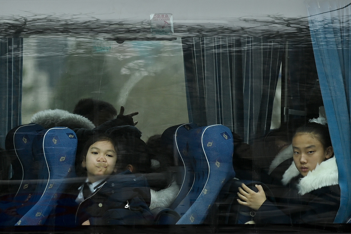 A child presses her face agasint the window of a bus in Beijing on Jan. 30. (Wang Zhao/AFP/Getty Images)