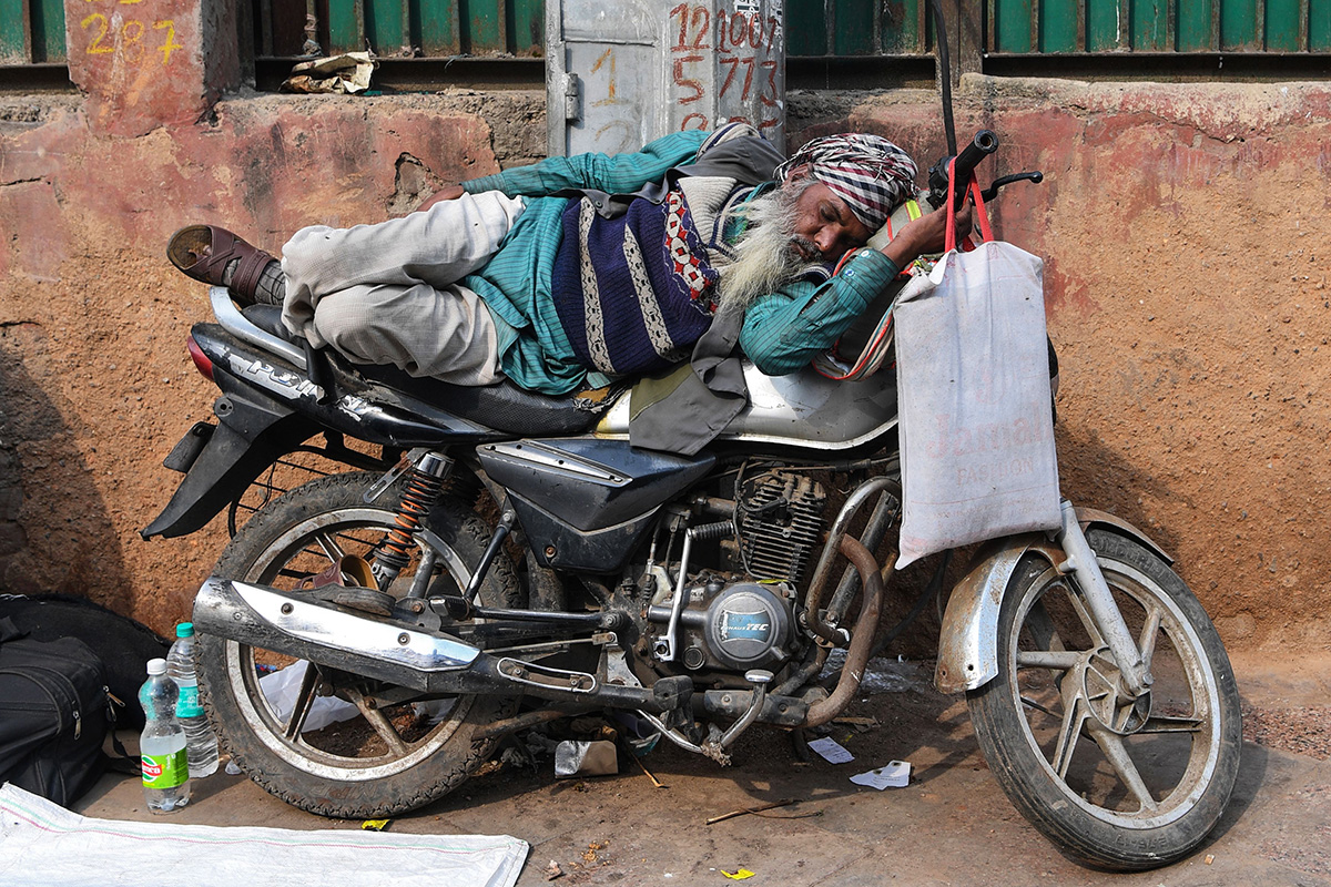 An Indian man sleeps on a motorbike in the old quarters of New Delhi on Jan. 30. (Sajjad Hussain/AFP/Getty Images)