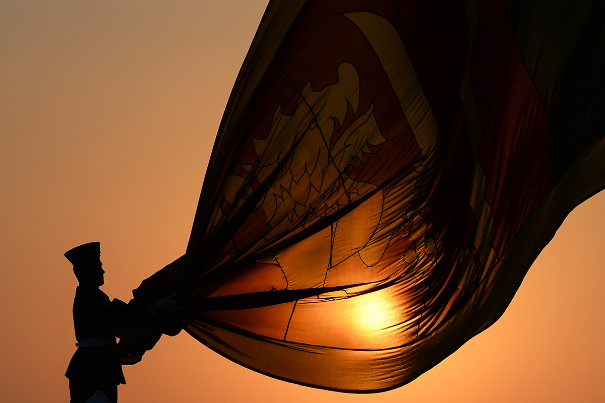 Sri Lankan Air force officers hold the national flag while it is lowered as part of a daily ceremony during sunset at the Galle Face Green promenade in Colombo on Jan. 30. (Lakruwan Wanniarachchi/AFP/Getty Images)