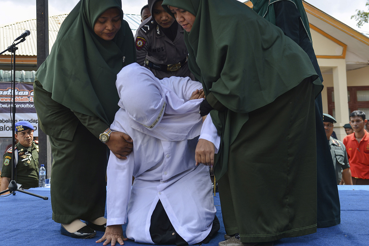 An 18-year-old Indonesian woman is assisted by police after being caned in public in Banda Aceh on Jan. 31 as punishment for being caught cuddling with her boyfriend, a crime under the region's Islamic law. (Chaideer Mahyuddin/AFP/Getty Images)