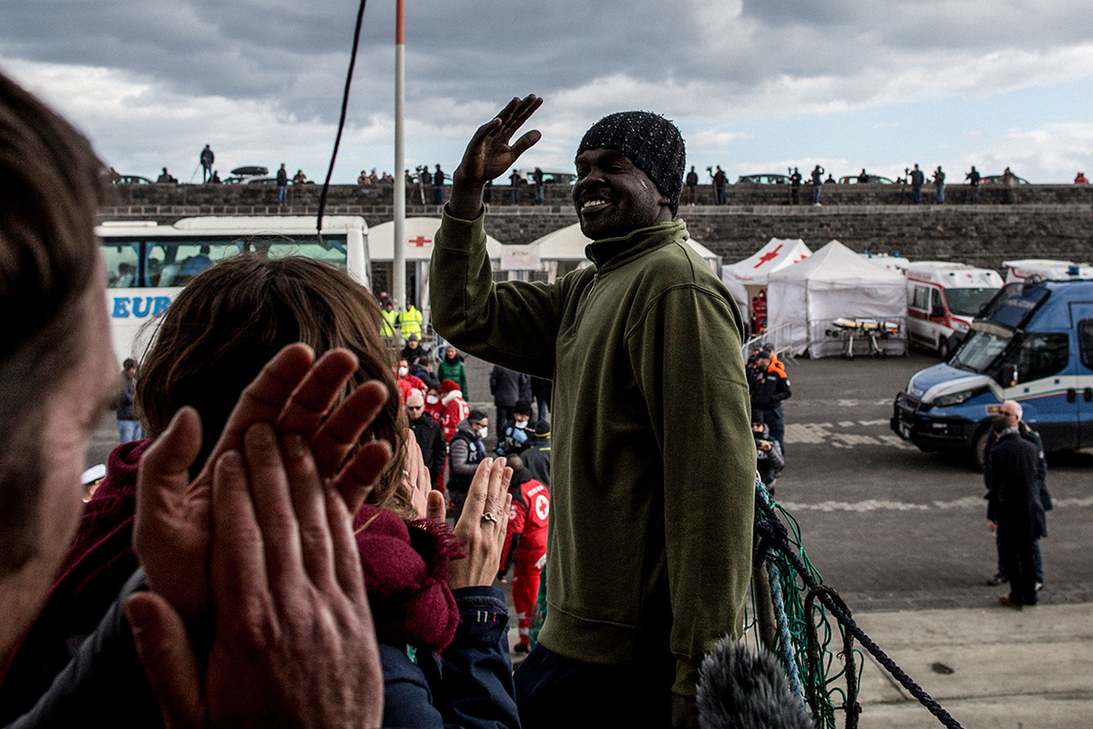 A migrant waves goodbye to the ship's crew and volunteers as he disembarks from a Dutch-flagged rescue vessel after it docked in the Sicilian port of Catania, Italy, on Jan. 31. (Federico Scoppa/AFP/Getty Images)