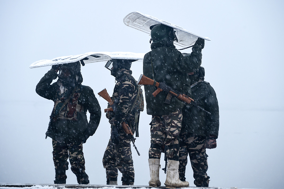 Indian paramilitary personnel stand guard on the shore of the Dal lake during heavy snowfall in Srinagar on Jan. 31. TAUSEEF MUSTAFA/AFP/Getty Images