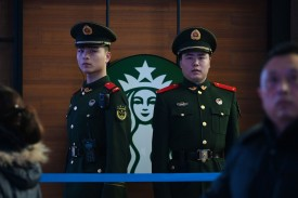 Paramilitary police officers stand guard near a Starbucks in the Beijing Railway Station on Feb. 2 ahead of the Lunar New Year. (Greg Baker/AFP/Getty Images)
