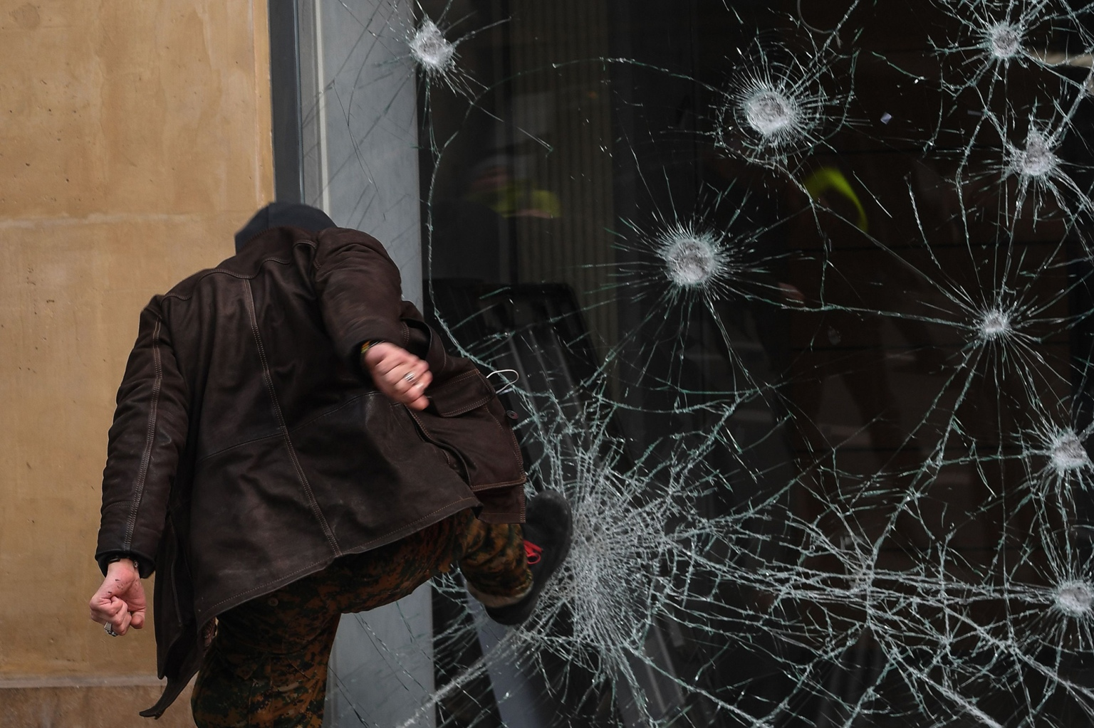 A person smashes the window of a bank a during a day of strikes called by the General Confederation of Labour French worker's union in Paris on Feb. 5. (Alain Jocard/AFP/Getty Images)