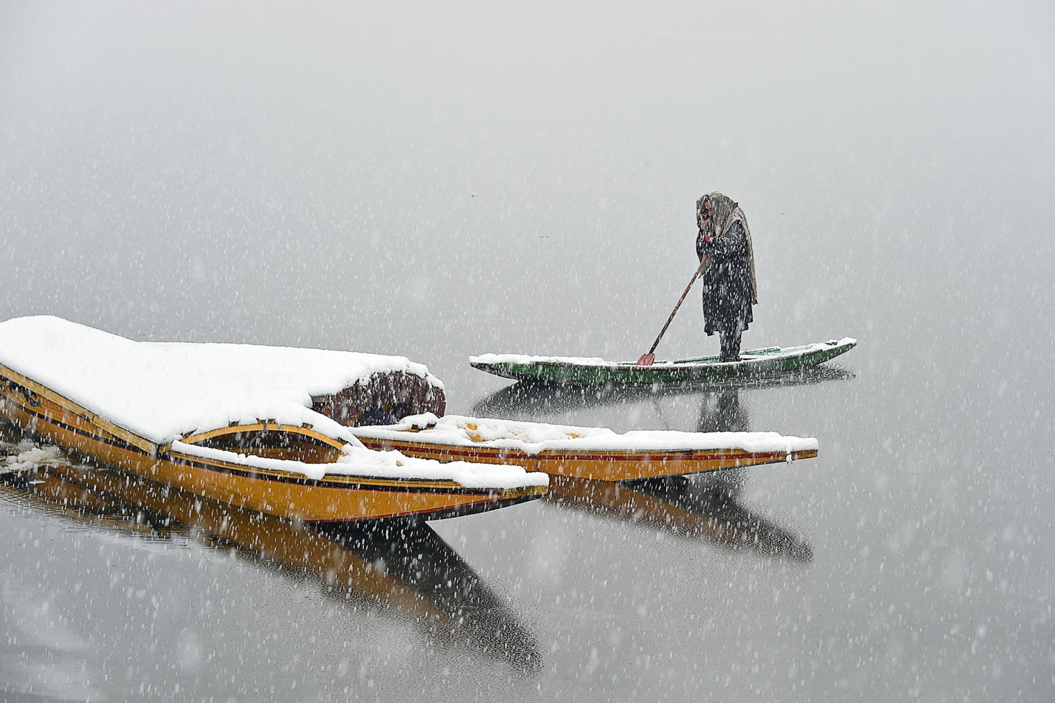 A Kashmiri boatman talks on a mobile phone during a snowfall at Dal Lake in Srinagar on Feb. 7. (Tauseef Mustafa/AFP/Getty Images)