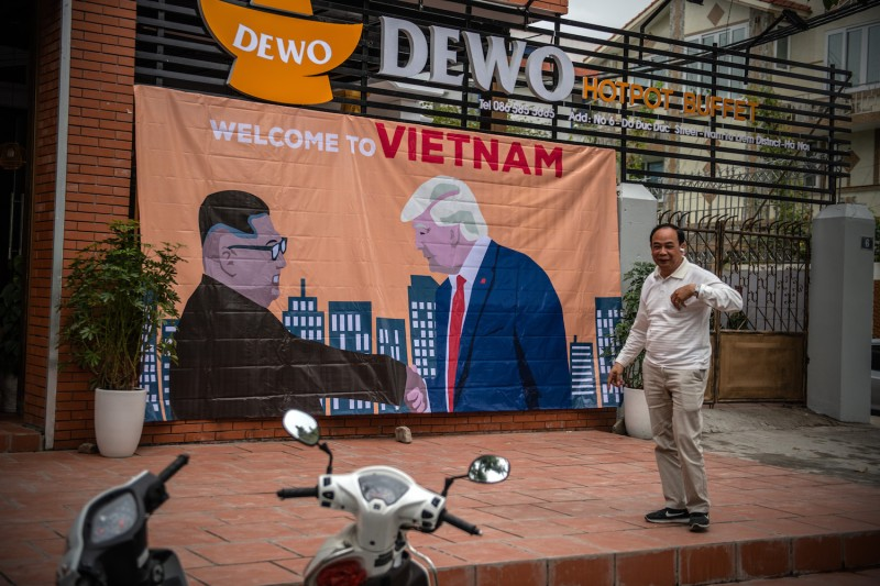 A man pauses by a banner showing U.S President Donald Trump and North Korean leader Kim Jong Un shaking hands next to the words 'Welcome to Vietnam' hung opposite the Marriott Hotel where President Trump is expected to stay during the forthcoming DPRK-USA summit. (Photo by Carl Court/Getty Images)