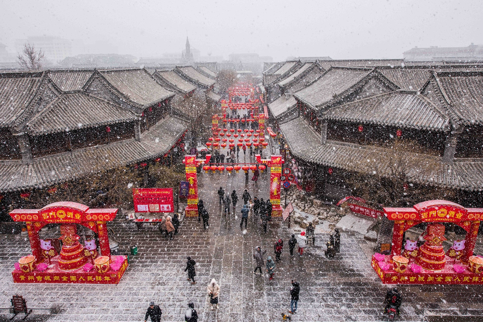 People walk under red lanterns in the snow at a scenic area during the Chinese Spring Festival holiday in Qingzhou, China, on Feb. 7. (VCG via Getty Images)