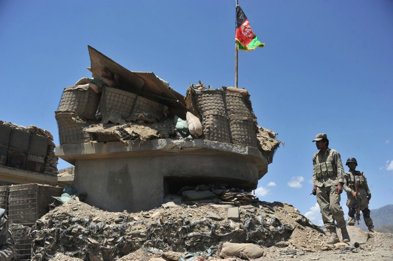 Afghan border policemen walk past a bunker destroyed during clashes with Pakistani troops in Nangarhar province on May 8, 2013. (Noorullah Shirzada/AFP/Getty Images)