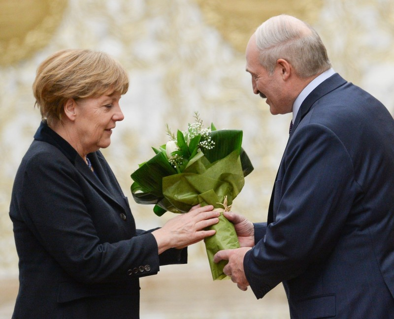 Belarus President Alexander Lukashenko, right, gives flowers to German Chancellor Angela Merkel at the presidential residence in Minsk on Feb. 11, 2015. (Maxim Malinovsky/AFP/Getty Images)