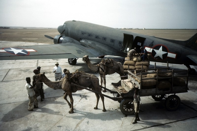 Local workers unload a Douglas Dakota Transport airplane at the U.S. Army Air Force Base in Karachi in July 1943. (Ivan Dmitri/Michael Ochs Archives/Getty Images)