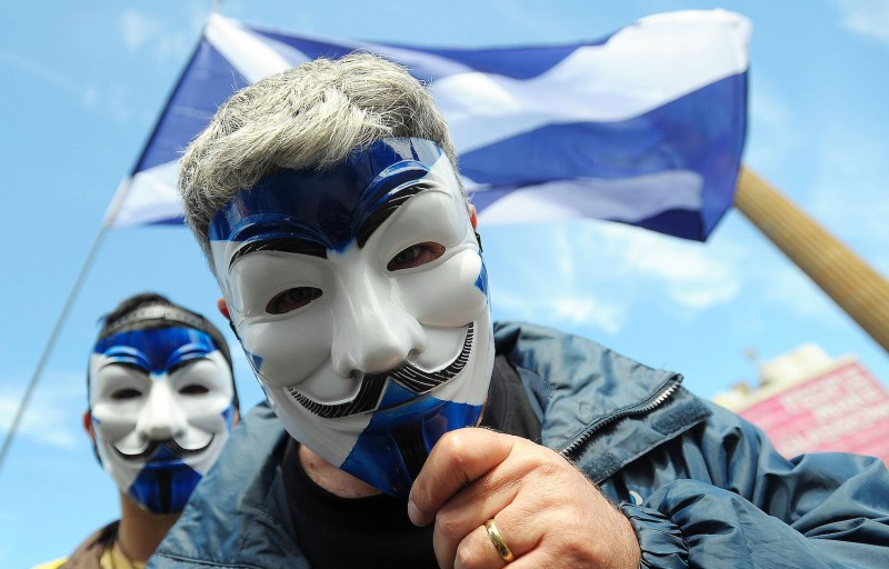 Pro-Scottish Independence supporters with Scottish Saltire flag masks pose for a picture at a rally to call for Scottish independence from the U.K. in George Square in Glasgow, Scotland, on July 30, 2016. (Andy Buchanan/AFP/Getty Images)