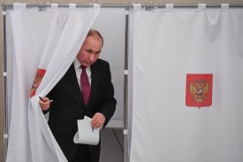 Vladimir Putin walks out of a voting booth at a polling station during Russia's presidential election in Moscow on March 18, 2018. (Yuri Kodobnov/AFP/Getty Images)