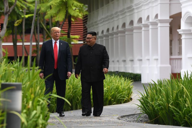 North Korean leader Kim Jong Un walks with U.S. President Donald Trump during a break in talks at their summit in Singapore on June 12, 2018. (Saul Loeb/AFP/Getty Images)