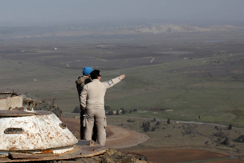 United Nations personnel stand at a lookout point as they monitor the Israel-Syria border in the  Golan Heights, on Jan. 21, 2019.