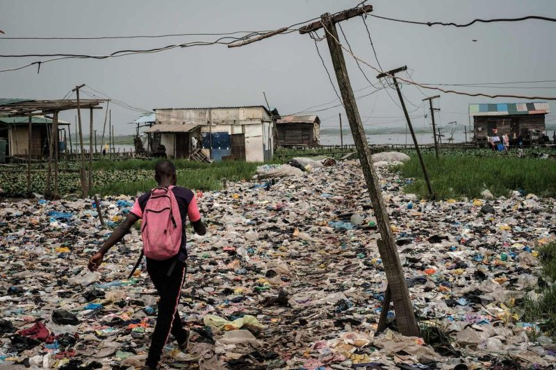 A Nigerian man walks on plastic waste in the Mosafejo area of Lagos on Feb. 12. (Yasuyoshi Chiba/AFP/Getty Images)