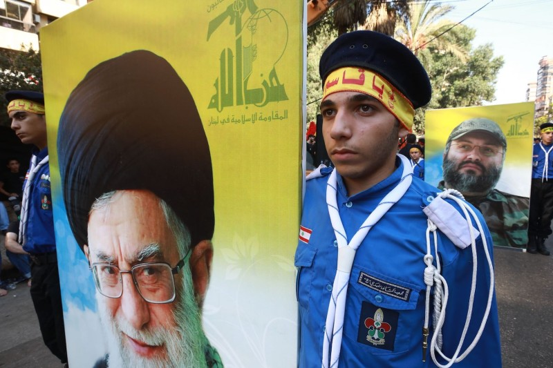 Supporters of  Hezbollah hold posters of Iran's Supreme leader Ayatollah Ali Khamenei and the movement's slain former military commander, Imad Mughniyeh, on Sept. 20, 2018 in Beirut.